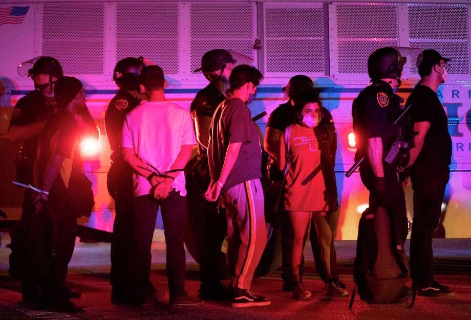 Protestors with handcuffs are detained on Tuesday, June 2, 2020, in downtown Houston during the fifth night of protests across the nation sparked by the death of former Houston resident George Floyd. Photo: Marie D. De Jesús, Staff Photographer / © 2020 Houston Chronicle