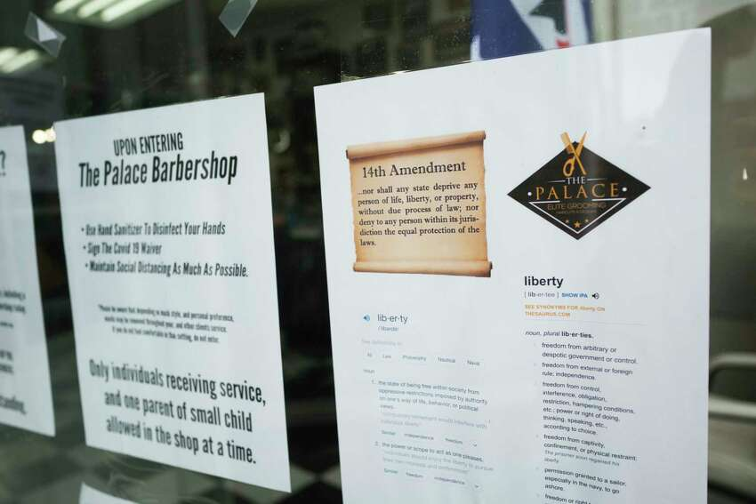 Informational postings on the window at The Palace Barbershop on Wednesday, June 3, 2020, in Rensselaer, N.Y. Wednesday was the first day that the shop could be back open to the public. The owner, Marlon Sousis is not requiring his employees or customers to wear a face mask in the barbershop. Sousis said that he believes it is every person's constitutional right to examine the data themselves and to decide what precautions they want to take. (Paul Buckowski/Times Union)