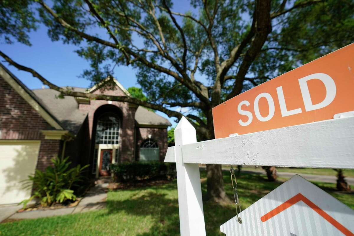 A sold sign is shown on a real estate sign outside a home Tuesday, March 31, 2020, in Spring. For the first time since the onset of the coronavirus pandemic, home sales have increased.