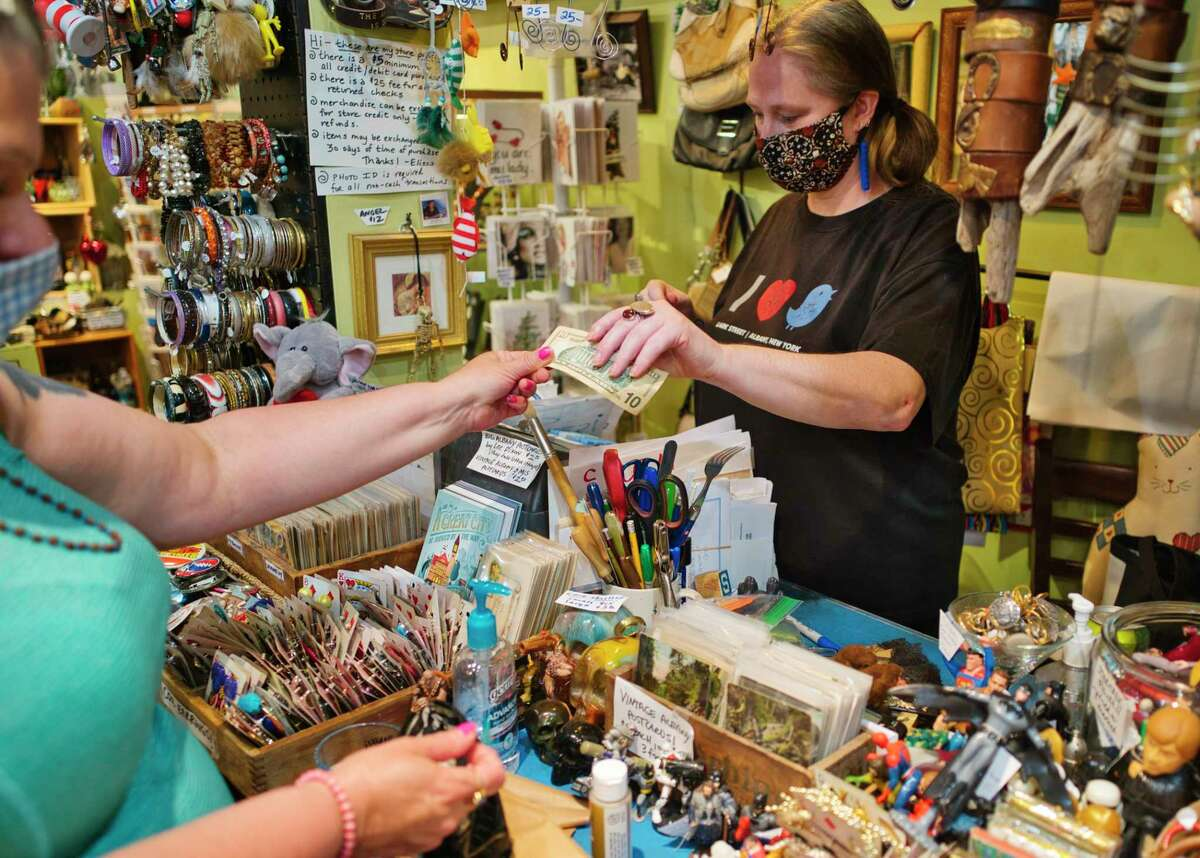 Elissa Halloran, owner of Elissa Halloran Designs on Lark Street makes her first sale on the first day she can reopen for business on Wednesday, June 3, 2020, in Albany, N.Y. (Paul Buckowski/Times Union)