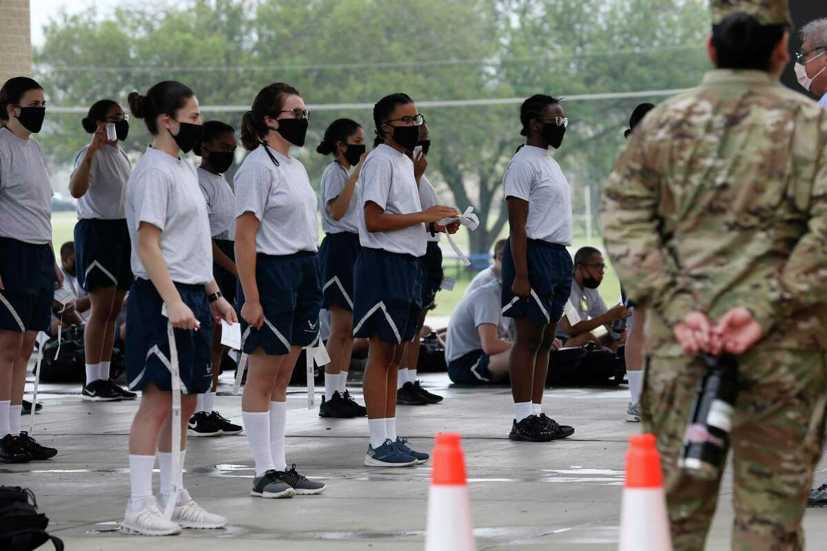 Out of their 14-day Restriction-of-Movement (ROM) quarantine, basic military trainees are lined up to enter the Reid Health Services Center for their medical processing at Joint Base San Antonio-Lackland, Wednesday, April 22, 2020.