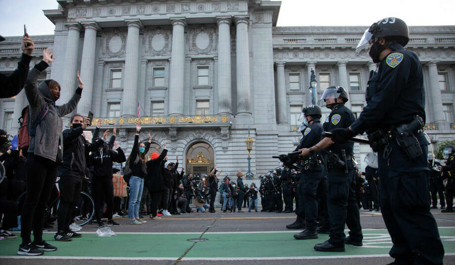 Protesters and police square off in front of San Francisco City Hall after the 8 PM curfew went into effect, Sunday, May 31, 2020, the third day of Bay Area unrest over the George Floyd killing in Minneapolis. The encounter remained tense but peaceful. Photo: MediaNews Group/The Mercury News/MediaNews Group Via Getty Images / Bay Area News Group