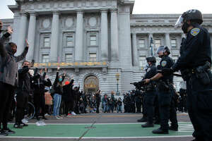 Protesters and police square off in front of San Francisco City Hall after the 8 PM curfew went into effect, Sunday, May 31, 2020, the third day of Bay Area unrest over the George Floyd killing in Minneapolis. The encounter remained tense but peaceful.