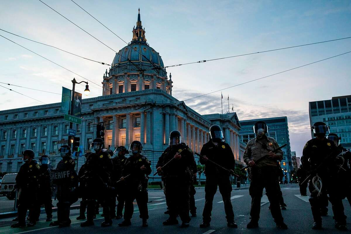 Police officers stand guard in front of City Hall after dispersing the crowd during a protest over the police killing of George Floyd, in San Francisco, California on May 31, 2020.