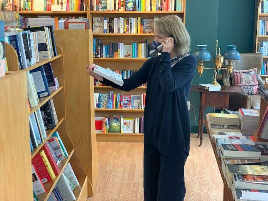 Staff member Sally Lovegrove selecting a book at Barrett Bookstore in Darien Photo: Contributed Photo / Connecticut Post