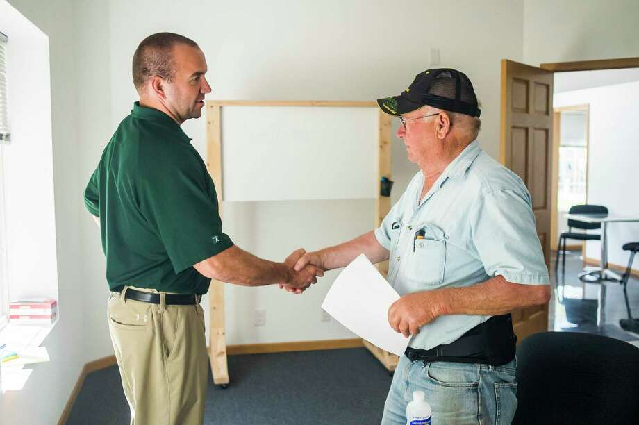Robert Kurchak, right, shakes hands with Scott McFarland of the Michigan Flood Victims Legal Team, left, after chatting Wednesday in their office at 2740 N. Meridian Road in Sanford. The team is assisting flood victims as they navigate their insurance claims, and also by putting together a class action suit. (Katy Kildee/kkildee@mdn.net)