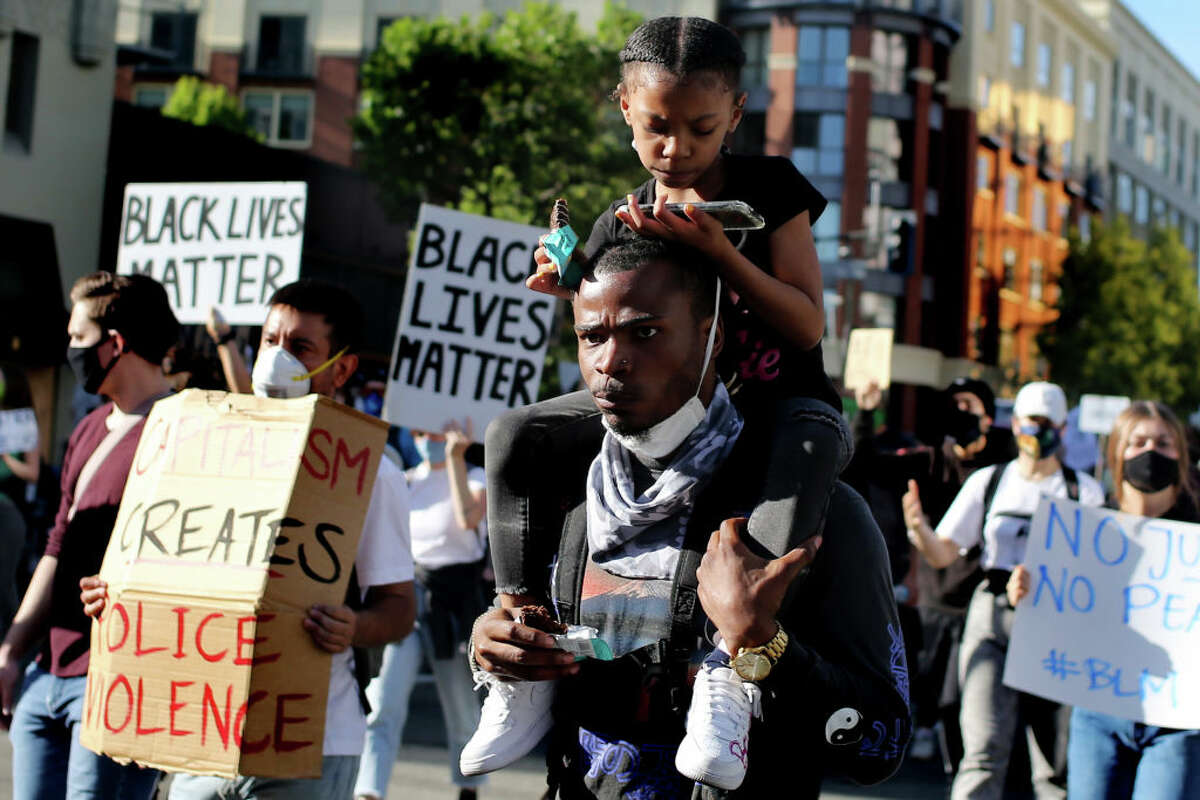 Robert Paig with his daughter Kyhree, 7, on his shoulders march down Broadway from Oakland Tech High School to Frank Ogawa Plaza during the fourth day of protests over George Floyd's death by the Minneapolis police in Oakland, Calif., on Monday, June 1, 2020.