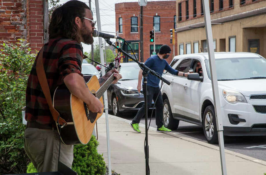 """Local musician Jared Unfried performs outside in the pocket park between Germania Brew Haus and Jacoby Arts Center as part of the art organization's """"Curbside Concert"""" series held at various locations in the city throughout the month of June. Photo: Jeanie Stephens  The Telegraph"""