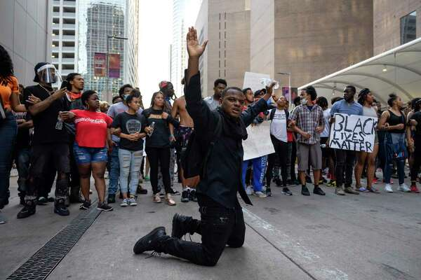 A demonstrator stands on his knees during a rally in downtown Houston to honor George Floyd, on Saturday, May 30, 2020. Floyd was killed by police in Minneapolis earlier this week.