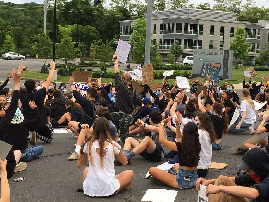 Young people, mostly high school students, stage a sit-in in front of town hall and police headquarters after the march to end racism in Wilton, CT on June 2, 2020. Photo: Jeannette Ross / Hearst Connecticut Media / Wilton Bulletin