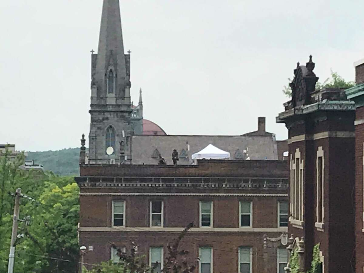 A Troy police officer in SWAT gear stands Wednesday on the roof of the police station at 55 State St.,Troy, New York where two canopy tents have been erected as the city police department prepares for possible protests.