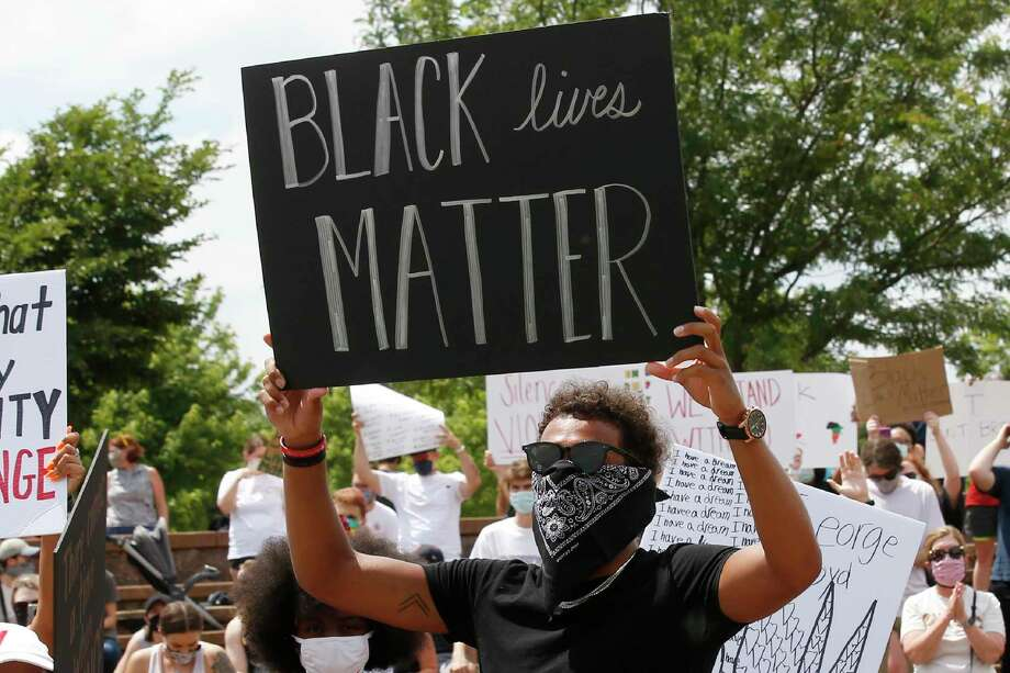"Atlanta Hawks guard Trae Young, right, holds a ""Black Lives Matter"" sign at a peaceful rally Monday in his hometown of Norman, Okla., calling attention to the killing of George Floyd by Minneapolis police. Photo: Sue Ogrocki, STF / Associated Press / Copyright 2020 The Associated Press. All rights reserved."