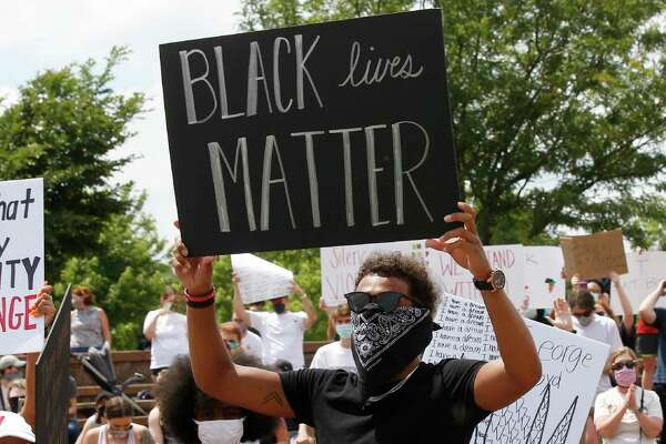 """Atlanta Hawks guard Trae Young, right, holds a """"Black Lives Matter"""" sign at a peaceful rally Monday in his hometown of Norman, Okla., calling attention to the killing of George Floyd by Minneapolis police."""