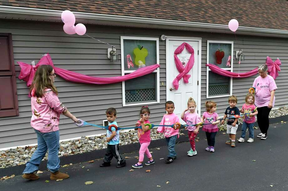Teachers lead 2-year-olds to the playground at the Teddy Bear Treehouse Learning Center in Seymour in October, 2017. The building was decorated with pink ribbons and balloons for the 7th annual Seymour Pink Day, which raises awareness and shows support for breast cancer. Photo: Peter Hvizdak / Hearst Connecticut Media / New Haven Register