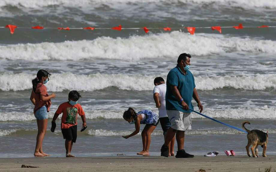 A family wears face masks while walking on the beach Sunday, May 24, 2020, in Galveston, Texas. Photo: Godofredo A. Vásquez, Houston Chronicle / Staff Photographer / © 2020 Houston Chronicle