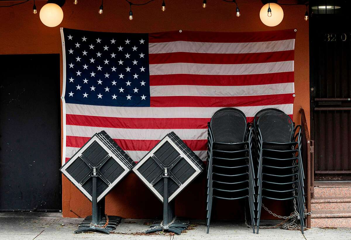 Chairs and tables are stacked in front of an American flag at a closed restaurant in New York on April 27 during the coronavirus pandemic.