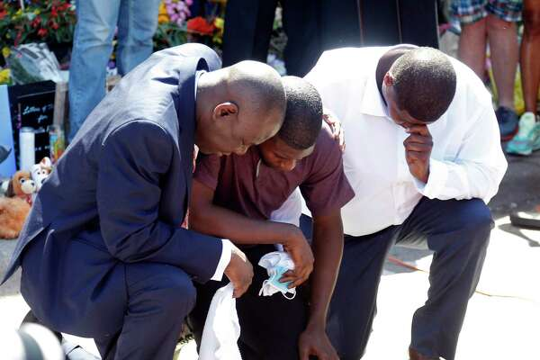 Quincy Mason, center, the son of George Floyd, and family attorney Ben Crump, left, kneel, Wednesday, June 3, 2020 as they visited the site of a memorial in Minneapolis where Floyd was arrested on May 25 and died while in police custody. Video shared online by a bystander showed a white officer kneeling on his neck during his arrest as he pleaded that he couldn't breathe.