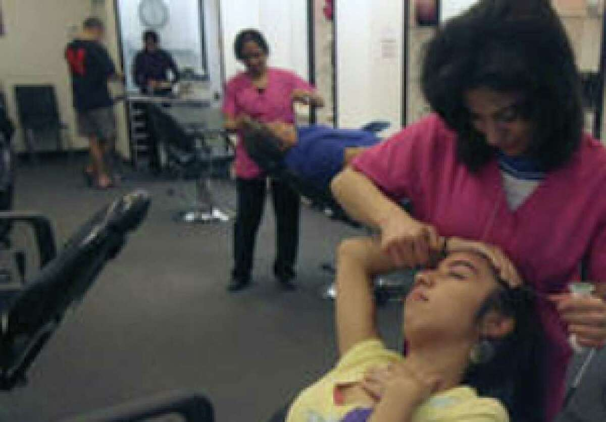 Mojgan Sabti performs an eyebrow shaping procedure called threading on Matreshka Mendez,19, at Just Stringz in North Star Mall. The process originated in South Asia and the Middle East.