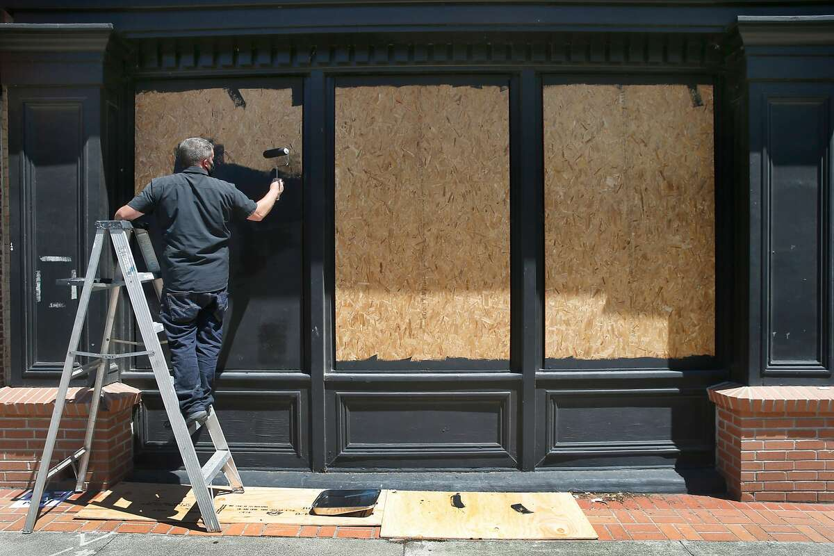 Mike Butler paints plywood boards covering the windows of an historic building on Georgia Street in Vallejo, Calif. on Wednesday, June 3, 2020. National Guard troops were deployed in Vallejo Tuesday night as the police station became overwhelmed by crowds massing in the streets.