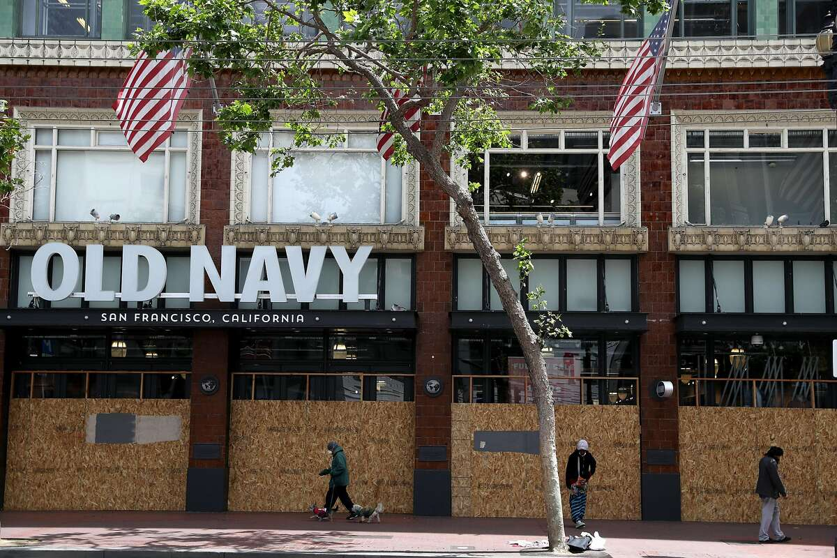 SAN FRANCISCO, CALIFORNIA - MAY 15: Pedestrians walk by a boarded up Old Navy store on May 15, 2020 in San Francisco, California. Malls and other businesses shutdown in an attempt to contain the coronavirus causing the U.S. retail sales to fall by a record 16.4% from March to April. (Photo by Justin Sullivan/Getty Images)