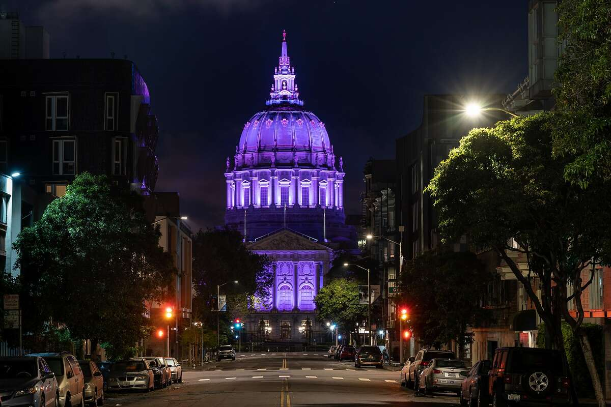 San Francisco City Hall is lighted in purple to honor hospitality workers as a car drives by on Monday, April 6, 2020, in San Francisco, Calif.