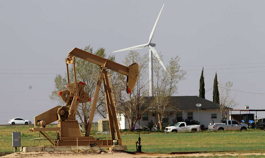 A house in Stanton, Texas has a pumpjack in front of it and a huge windmill behind it.  A new paper published today in the journal Environmental Health Perspectives shows that pregnant women in rural areas who lived within one kilometer of high-producing wells were 40% more likely to have low birth weight babies compared to those who lived further away. Photo: JOHN DAVENPORT/SAN ANTONIO EXPRESS-NEWS / ©San Antonio Express-News