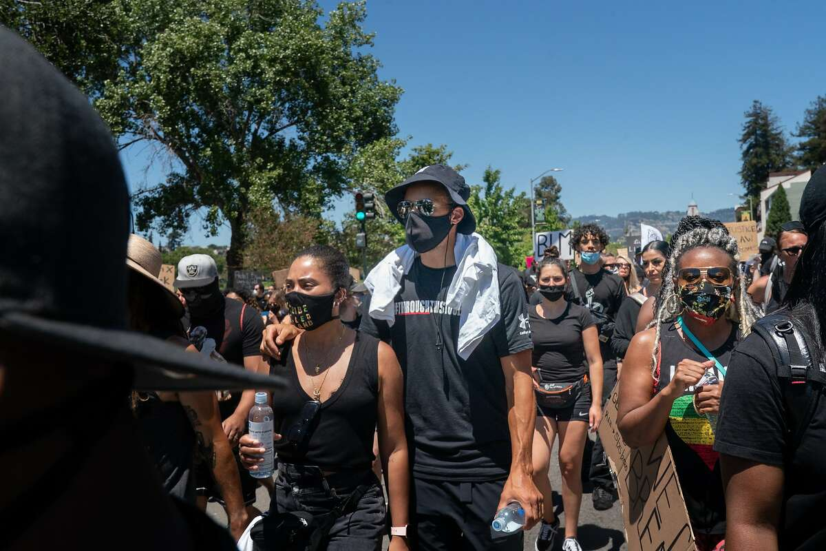 Stephen Curry with wife Ayesha march around Lake Merrit to protest the killing of George Floyd by Minneapolis Police in Oakland, Calif. Curry has begun a YouTube interview series to push for civic engagement.