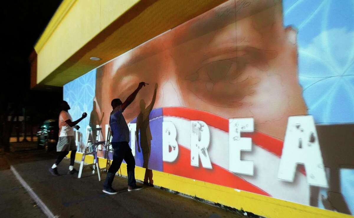 Matthew Jeanbaptiste, left, and Samson Adenugba work on tracing a new mural that is going up on the Breakfast Klub in Houston on Tuesday, June 2, 2020.