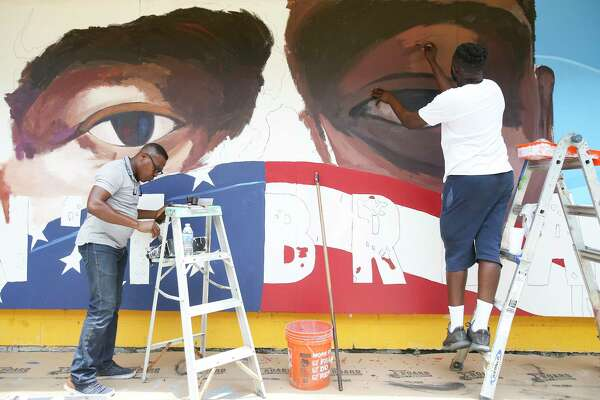Artists Samson Adenugba, left, and Matthew Jeanbaptiste work on a mural inspired by George Floyed, on the side of the Breakfast Klub in Midtown on Tuesday, June 2, 2020.