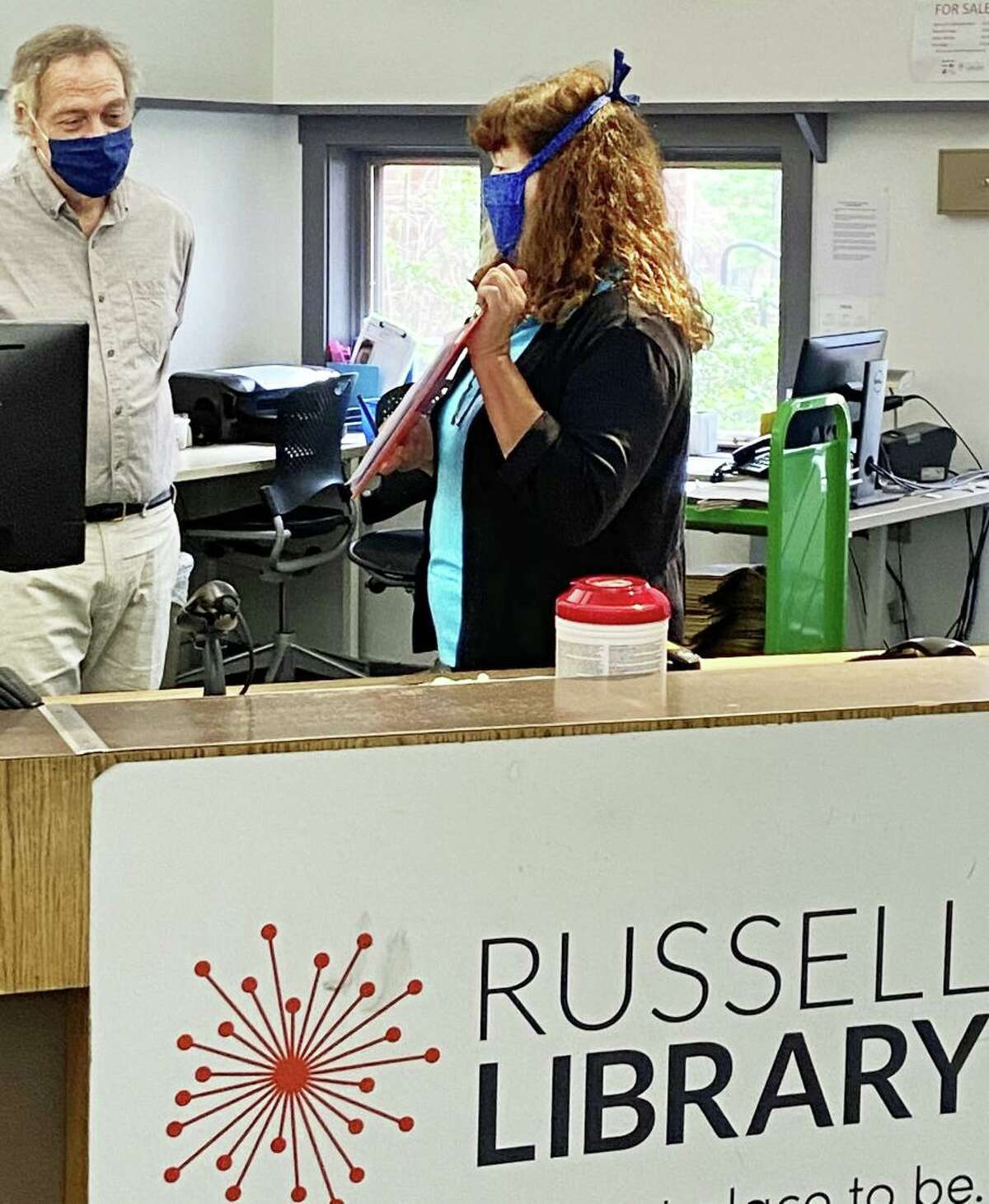Russell Library staff are hard at work behind the scenes at the 123 Broad St., Middletown, facility, readying for the return of patrons at a yet-to-be-determined date during the coronavirus pandemic. Here, employee Phil Delegan and Assistant Director for Public Services Mary Dattilo get up to speed Tuesday on how curbside pickup of materials will work.