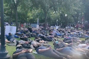"Protesters in Travis Park chanting ""I can't breath"" on the floor with their hands behind their backs during the fifth day of protests Wednesday afternoon, June 3, 2020, over the death of George Floyd."