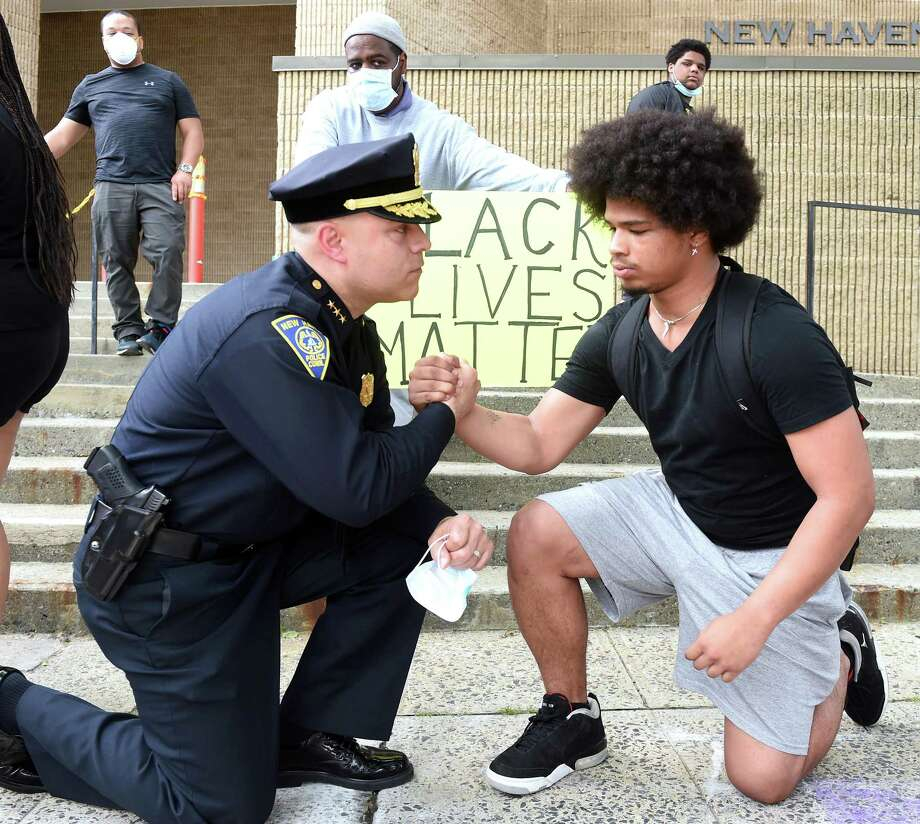 New Haven Police Chief Otoniel Reyes (left) takes a knee to the ground with Wilbur Cross junior Jabez Cubiz, 18, in front of the New Haven Police Department after the chief met with protesters on June 3. Photo: Arnold Gold / Hearst Connecticut Media / New Haven Register