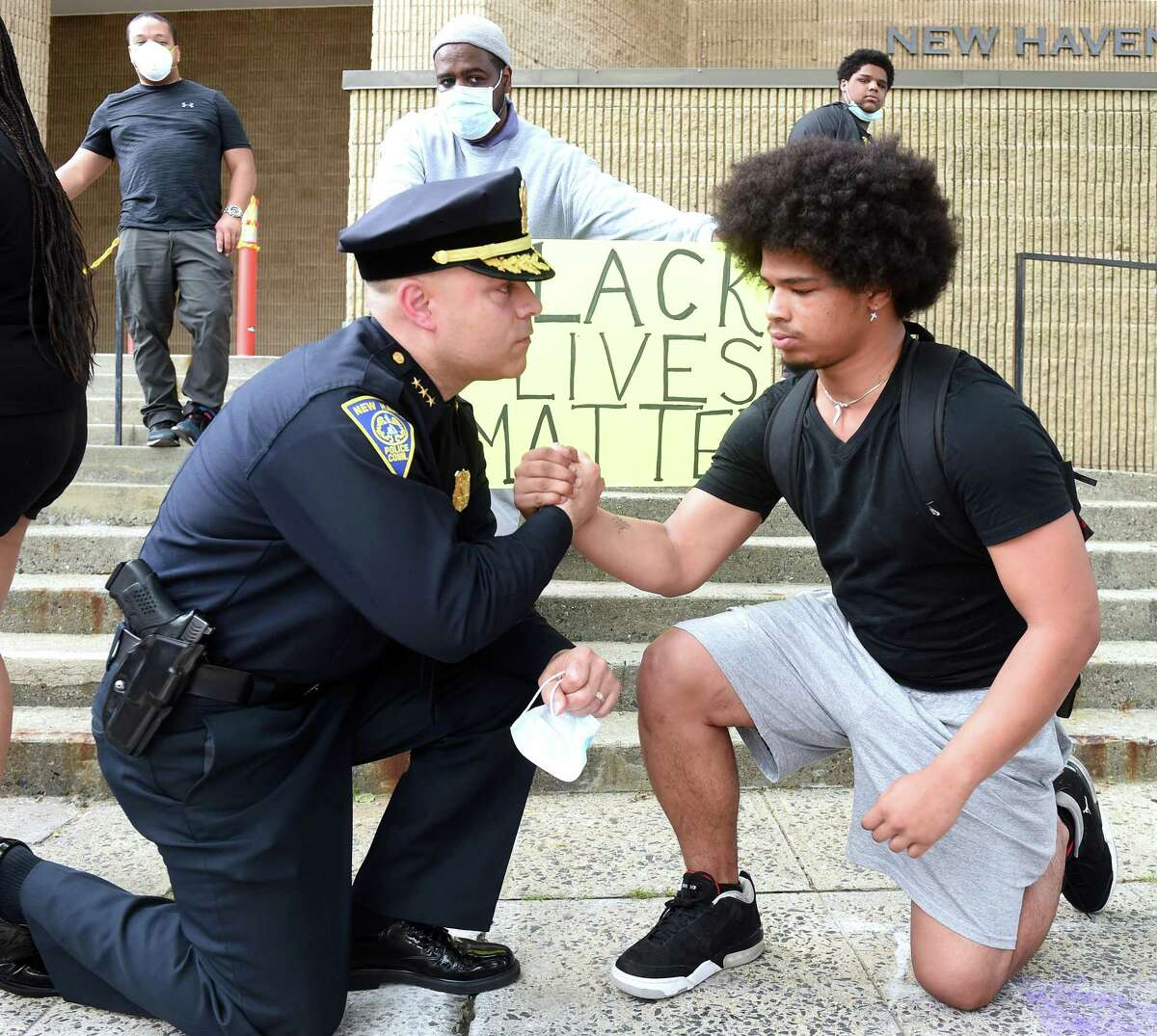 New Haven Police Chief Otoniel Reyes (left) takes a knee to the ground with Wilbur Cross junior Jabez Cubiz, 18, in front of the New Haven Police Department after the chief met with protesters on June 3, 2020 in the aftermath of the death of George Floyd at the hands of Minneapolis Police.