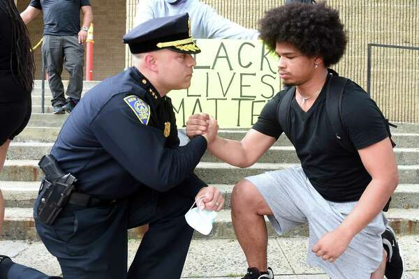 New Haven Police Chief Otoniel Reyes, left, takes a knee to the ground with Wilbur Cross junior Jabez Cubiz, 18, in front of the New Haven Police Department after the chief met with protesters on June 3, 2020.