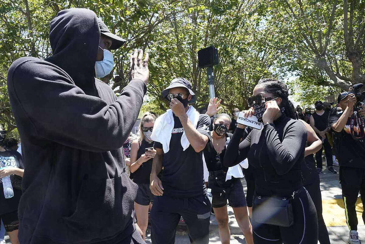 Kevon Looney waves to Ayesha Curry with Stephen, center, before they joined the march around Lake Merrit with other Warriors, Klay Thompson and Damion Lee to protest the killing of George Floyd by Minneapolis Police on Wednesday, June 3, 2020 in Oakland, Calif.