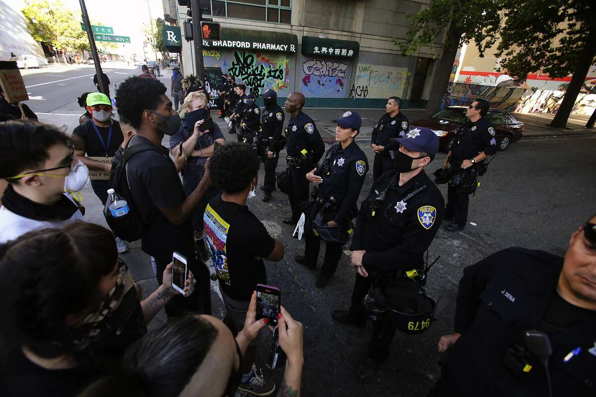 Several young demonstrators engaged with police at a roadblock on Broadway in a solidarity protest against police brutality and the killing of black citizens in Oakland, Calif.