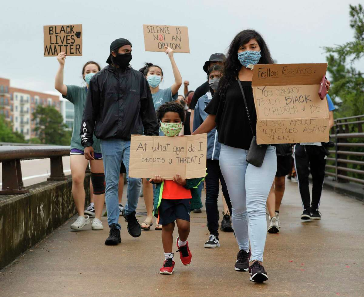 Hector Pina 6, walks beside his mother, Cristina, as protester march against the death of Houston native George Floyd along the Lake Woodlands Drive bridge near North Shore Park, Wednesday, June 3, 2020, in The Woodlands.