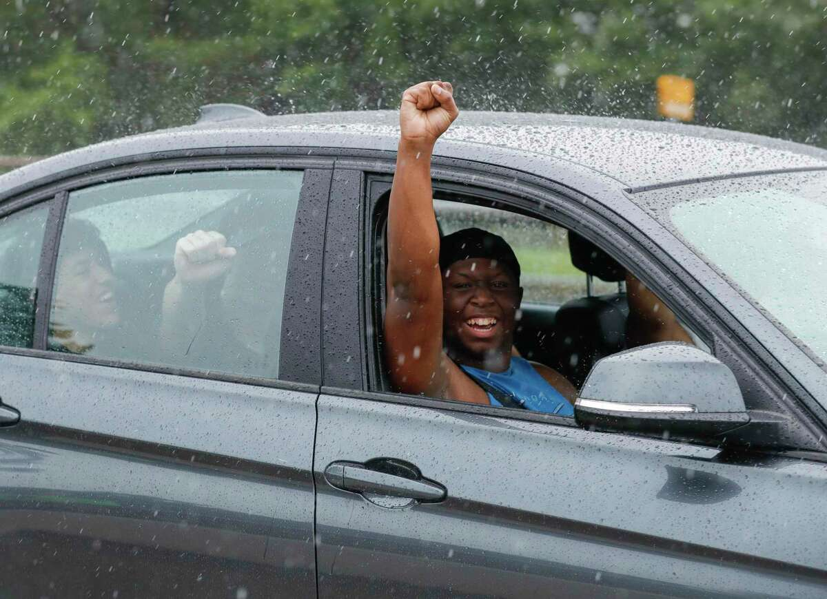 A man raises his fist toward protester as they march against the death of Houston native George Floyd along the Lake Woodlands Drive bridge near North Shore Park, Wednesday, June 3, 2020, in The Woodlands.