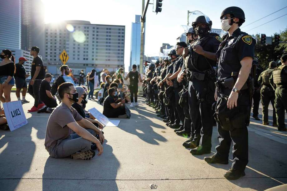 Demonstrators sit in front of Houston Police Department officers in downtown Houston, Tuesday, June 3, 2020. An estimated 60,000 people attended the rally in support of George Floyd and police reform. Photo: Gustavo Huerta, Staff Photographer / Houston Chronicle © 2020