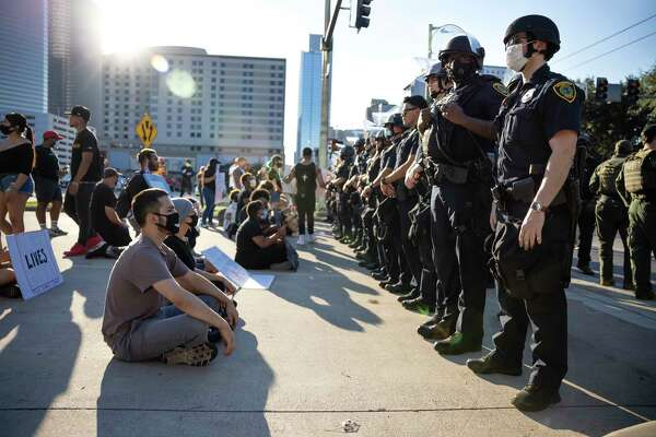 Demonstrators sit in front of Houston Police Department officers in downtown Houston, Tuesday, June 3, 2020. An estimated 60,000 people attended the rally in support of George Floyd and police reform.