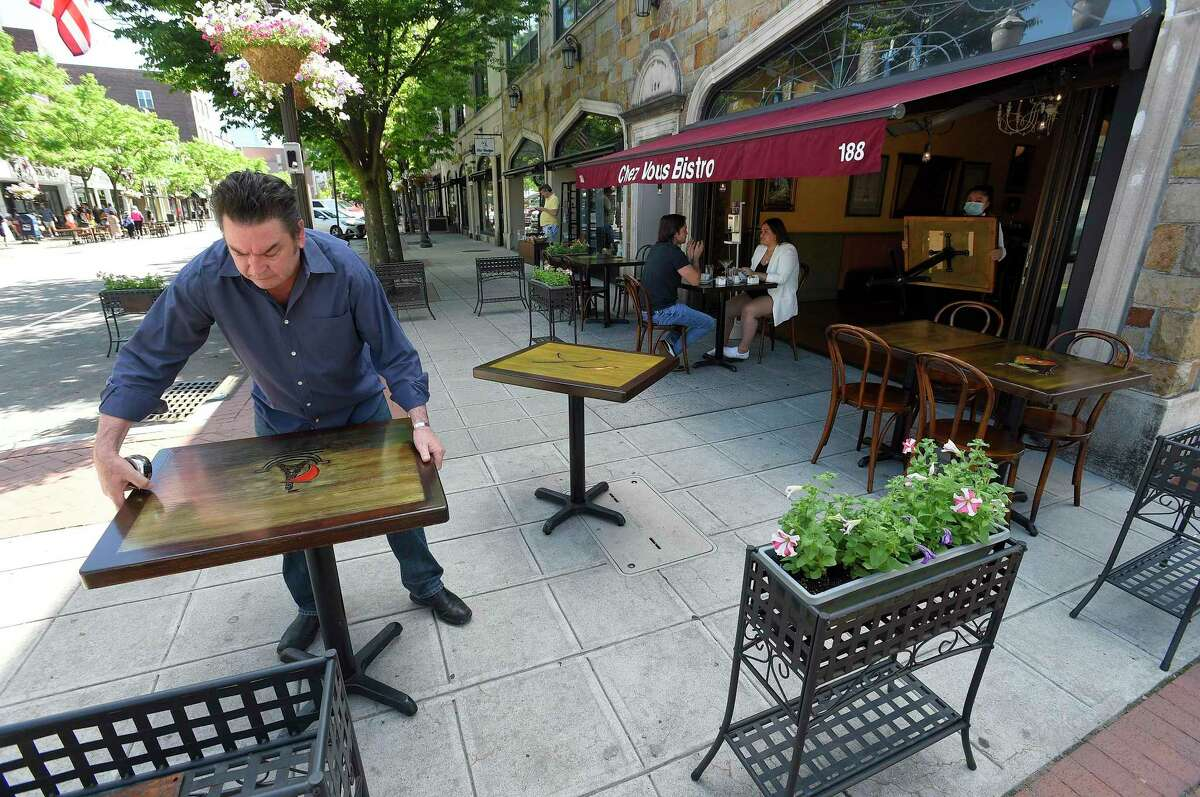 Owner Alain Bars of Chez Vous Bistro on Bedford Street sets up his extended outdoor dining area on May 30 in Stamford. Stamford Downtown Special Services transformed a few downtown streets, like Bedford Street, into Streateries, allowing area restaurants to extend their outdoor dining into parking spaces on the street for area residents to enjoy local dining as the state begins to reopen following a two month closure in response to the COVID-19 Pandemic.