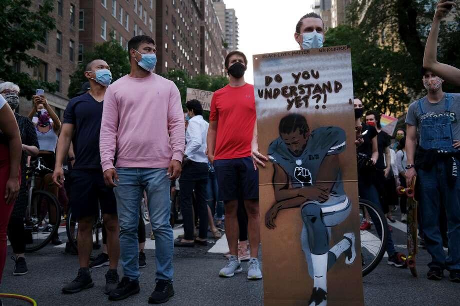 Un hombre muestra una pancarta en Nueva York con un dibujo de Colin Kaepernick, ex mariscal de campo de los 49ers de San Francisco, durante una manifestación por la muerte de George Floyd. Photo: Spencer Platt / Getty Images