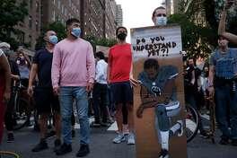 Un hombre muestra una pancarta en Nueva York con un dibujo de Colin Kaepernick, ex mariscal de campo de los 49ers de San Francisco, durante una manifestación por la muerte de George Floyd.