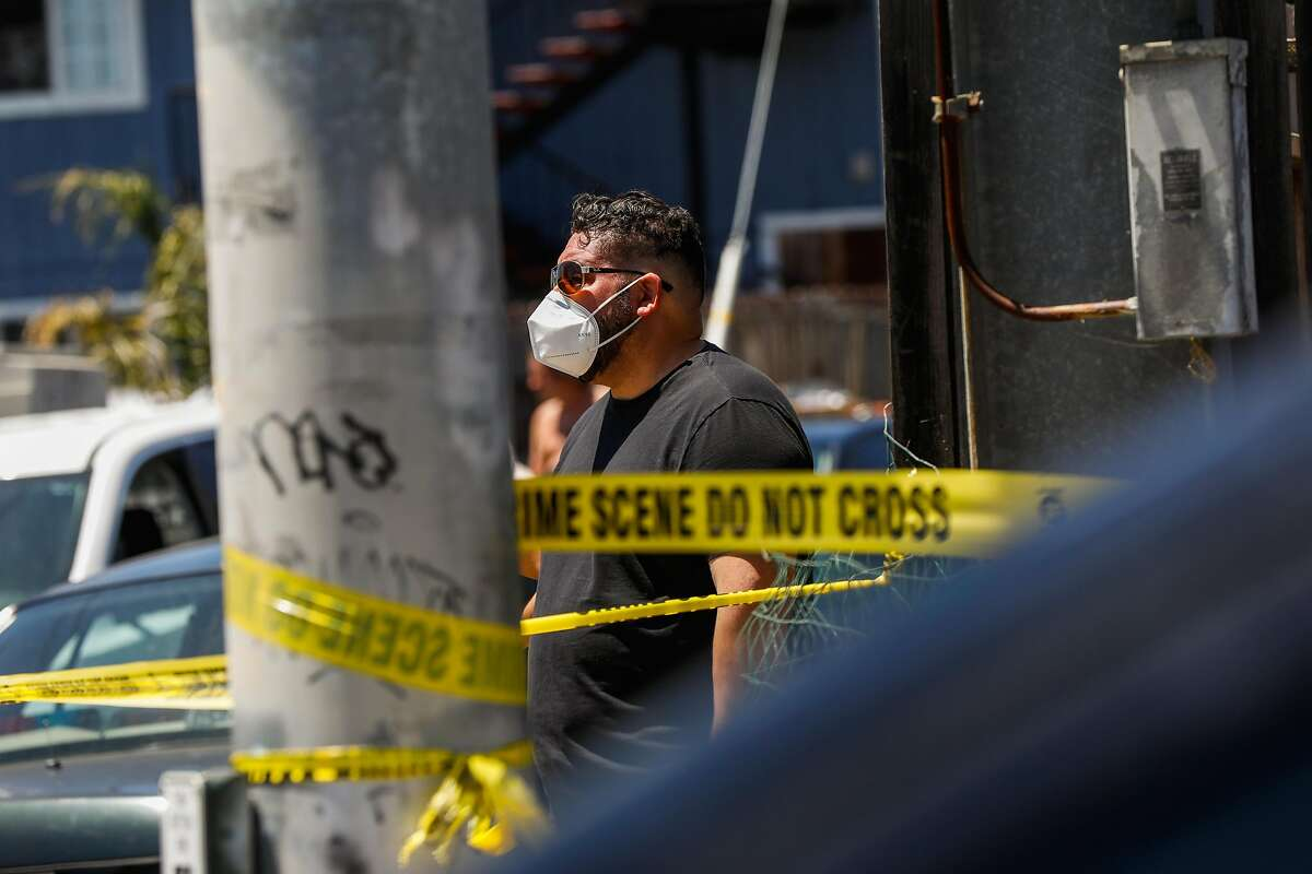 A bystander looks from behind the caution tape at a crime scene where a man reportedly was holding two children hostage on Wednesday, June 3, 2020 in Oakland,California.