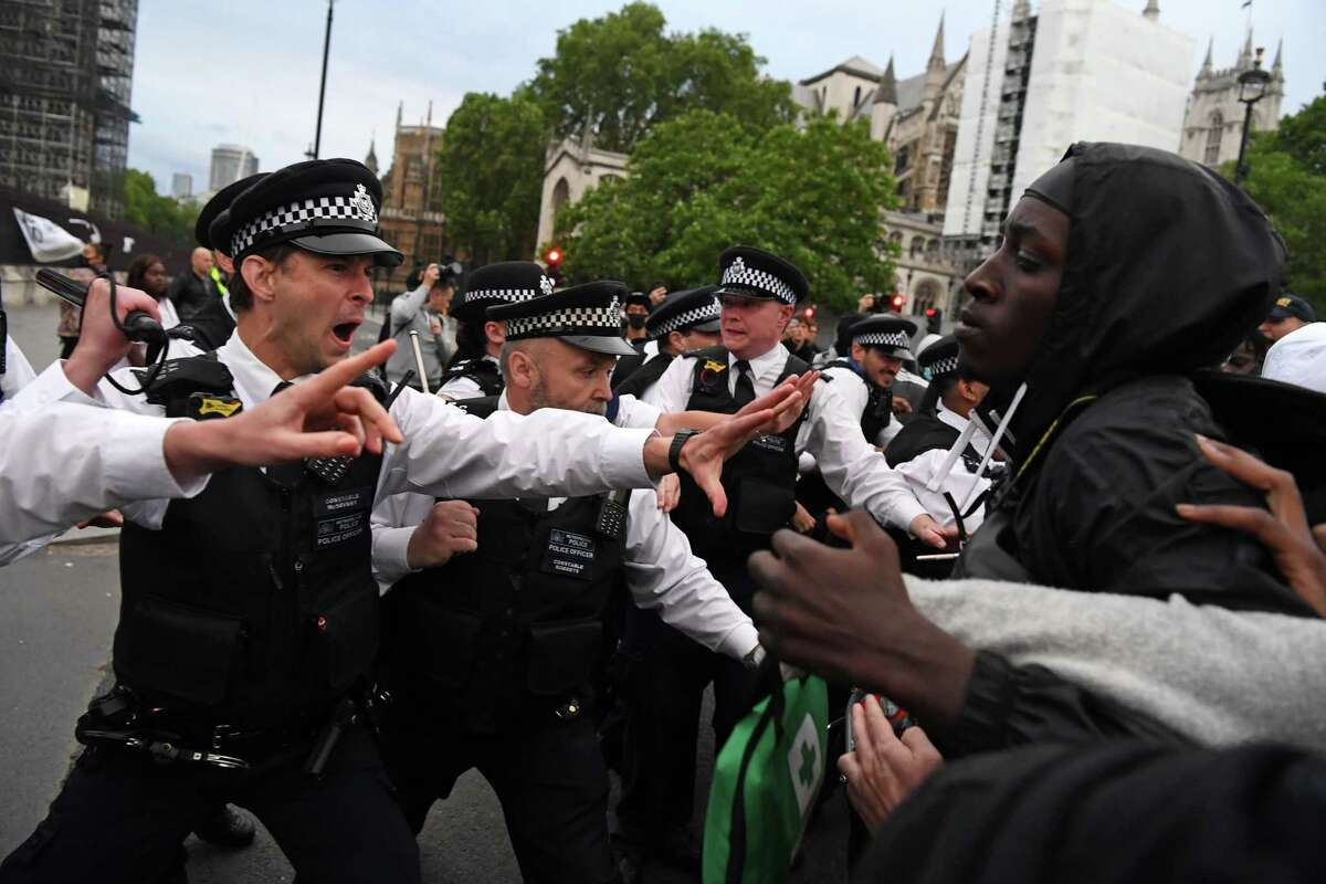 Protestors remonstrate with Police officers in Parliament Square, during an anti-racism demonstration in London, on June 3, 2020, after George Floyd, an unarmed black man died after a police officer knelt on his neck during an arrest in Minneapolis, USA. - Thousands of people took to the streets of London on Wednesday to protest the death of George Floyd in US police custody, as Prime Minister Boris Johnson condemned the killing and told President Donald Trump that racist violence had