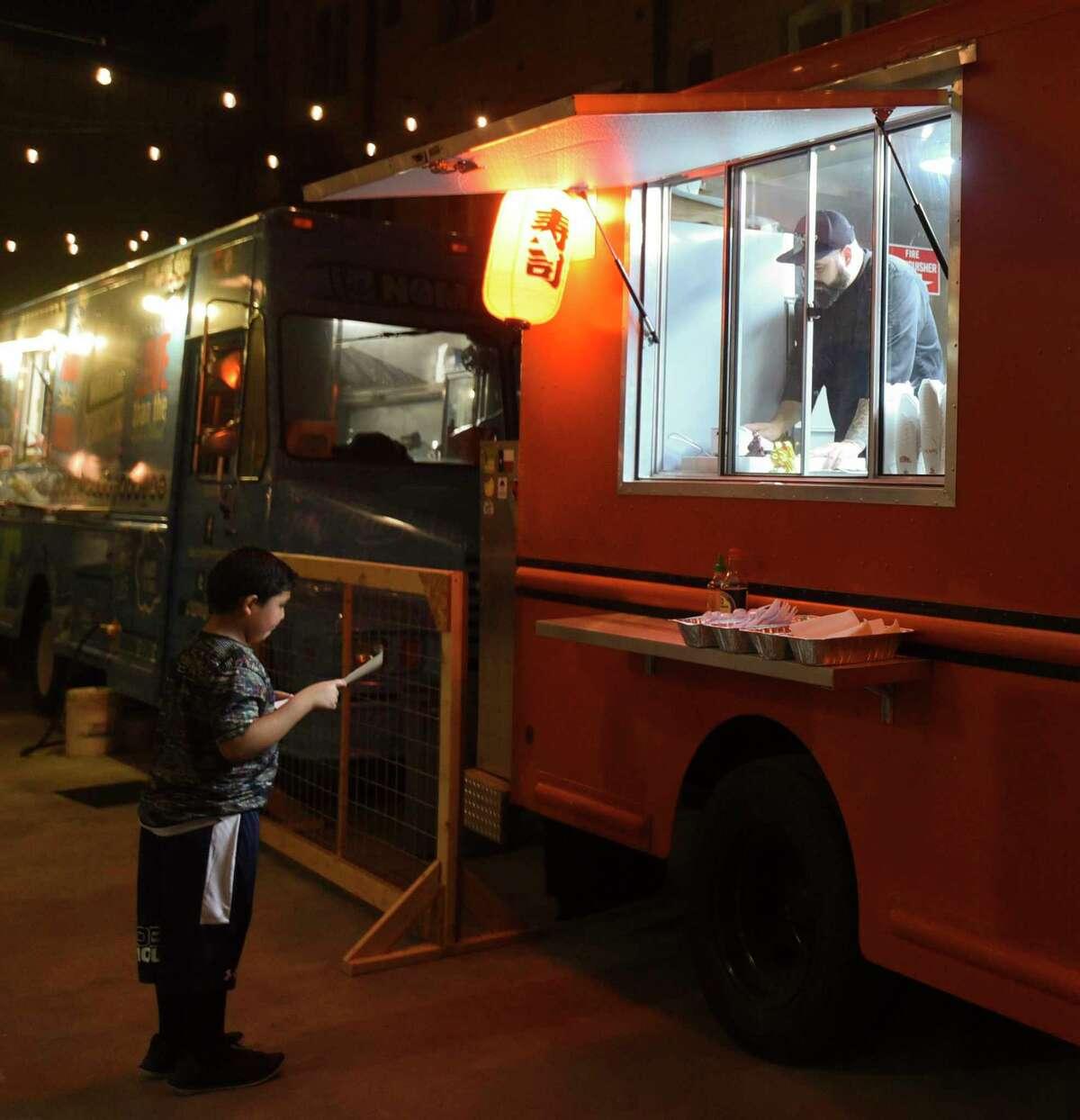 ARCHIVO- Clientes ordenan en el camión de comida Wok-A-Mole, el viernes 15 de febrero de 2019, en Cultura Beer Garden.