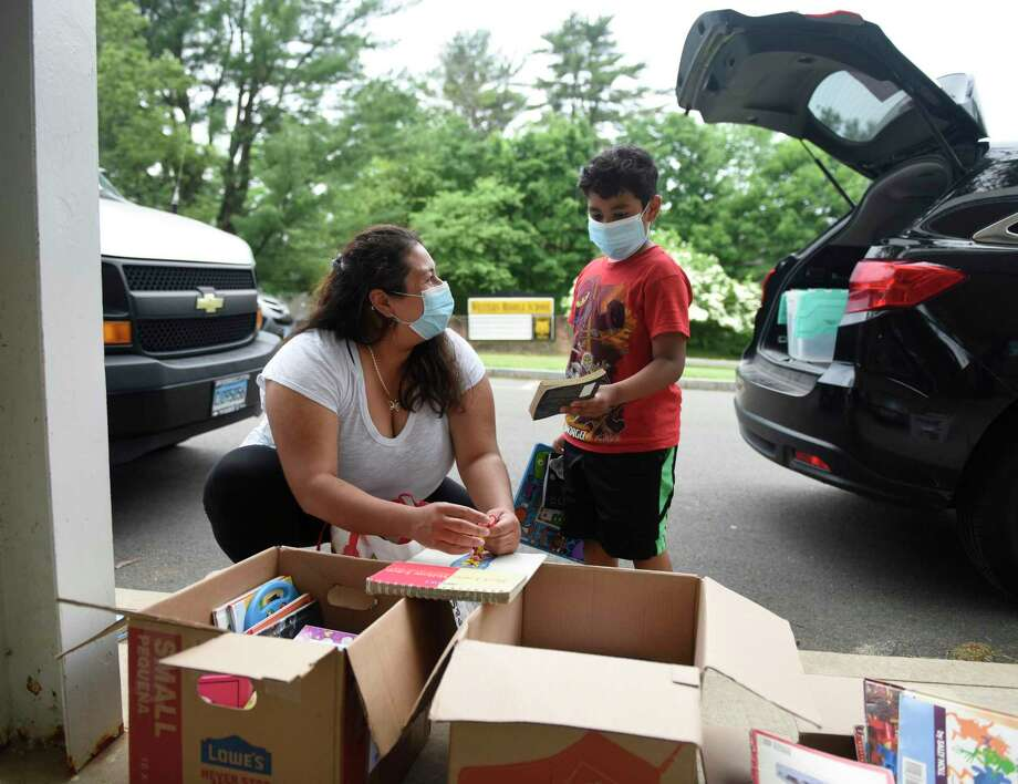 Janet Manzanarez and her son, Eduardo, a rising fourth-grader, pick out books given away by Girl Scout Troop 50681 at Western Middle School in Greenwich, Conn. Wednesday, June 3, 2020. 13 North Mianus School fifth-graders from Girl Scout Troop 50681 collected, cleaned, and catalogued more than 4,000 books that are now being donated to local students. The books have been available to pick up via the Greenwich Public Schools breakfast and lunch pickup program. The girls realized that with libraries closed, students would have a tough time accessing books this summer, so they decided to take action and organize the book drive. Photo: Tyler Sizemore / Hearst Connecticut Media / Greenwich Time