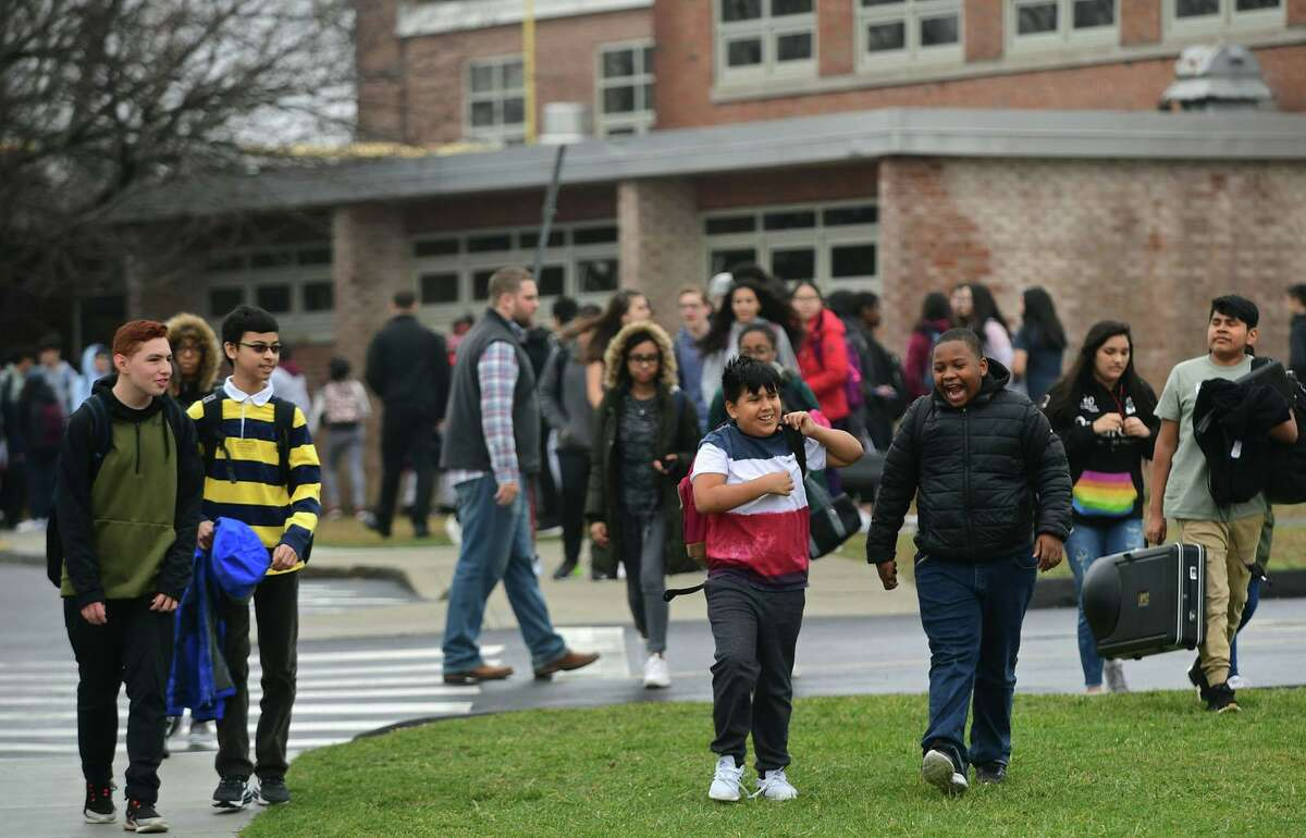 Students exit Nathan Hale Middle School after an early dismissal Friday, March 13, 2020, in Norwalk, Conn.