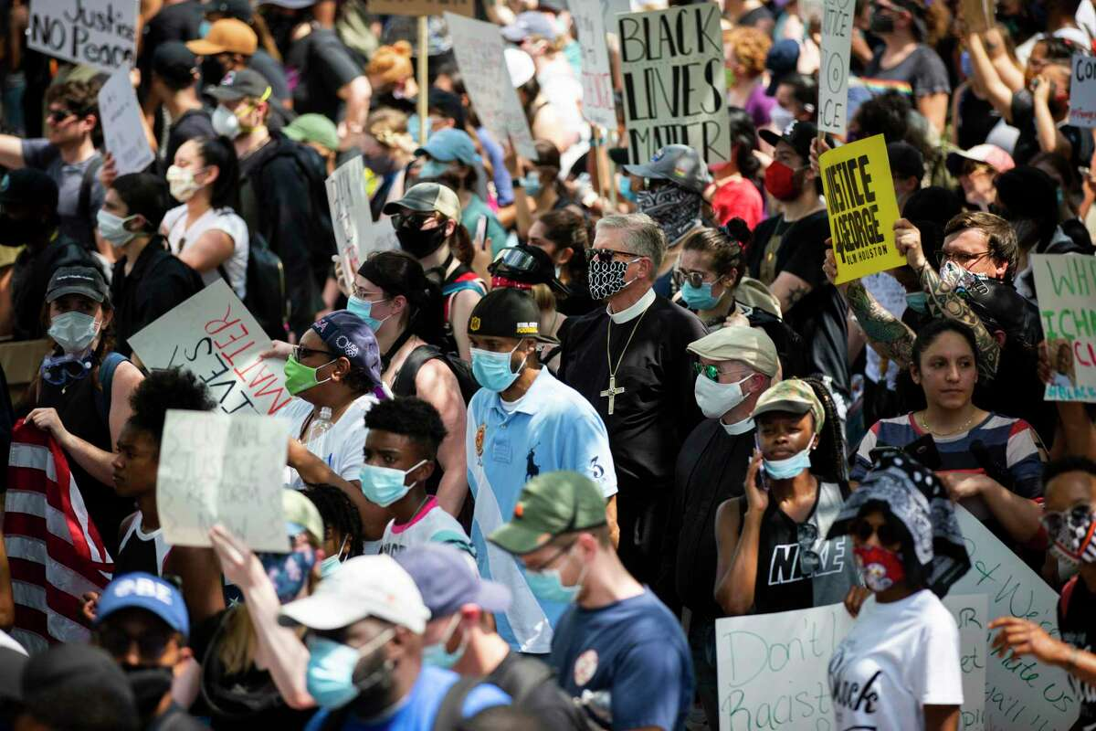 A faith leader joins thousands of demonstrators in support of George Floyd's family on Tuesday, June 2, 2020, in Houston.