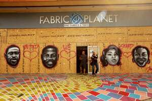 In this photo, Jack Sapar, owner of Fabric Planet, walks out of his business with a customer with the front windows boarded up today against more protests along Lincoln Blvd. in Venice on June 1. The boards features images of African-Americans who died at the hands of police including George Floyd, from left, Ahmaud Arbery, Breouna Taylor and Sandra Bland. The art was created by street artist MuckRock on June 1.